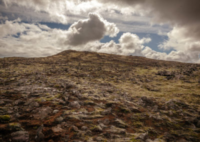 Walking across a lava field to reach the volcano.